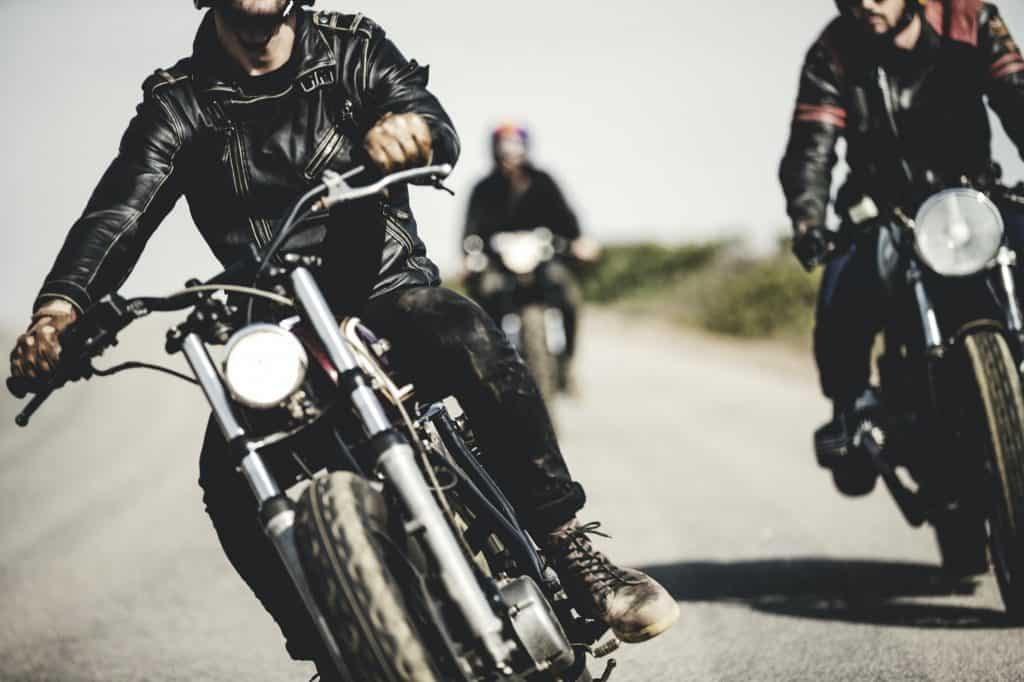 Three men wearing leather jackets riding cafe racer motorcycles along rural road.
