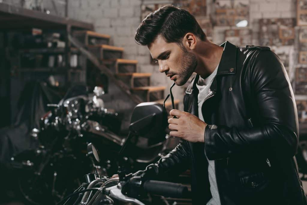 young handsome biker in black leather jacket with classic motorcycle in workshop