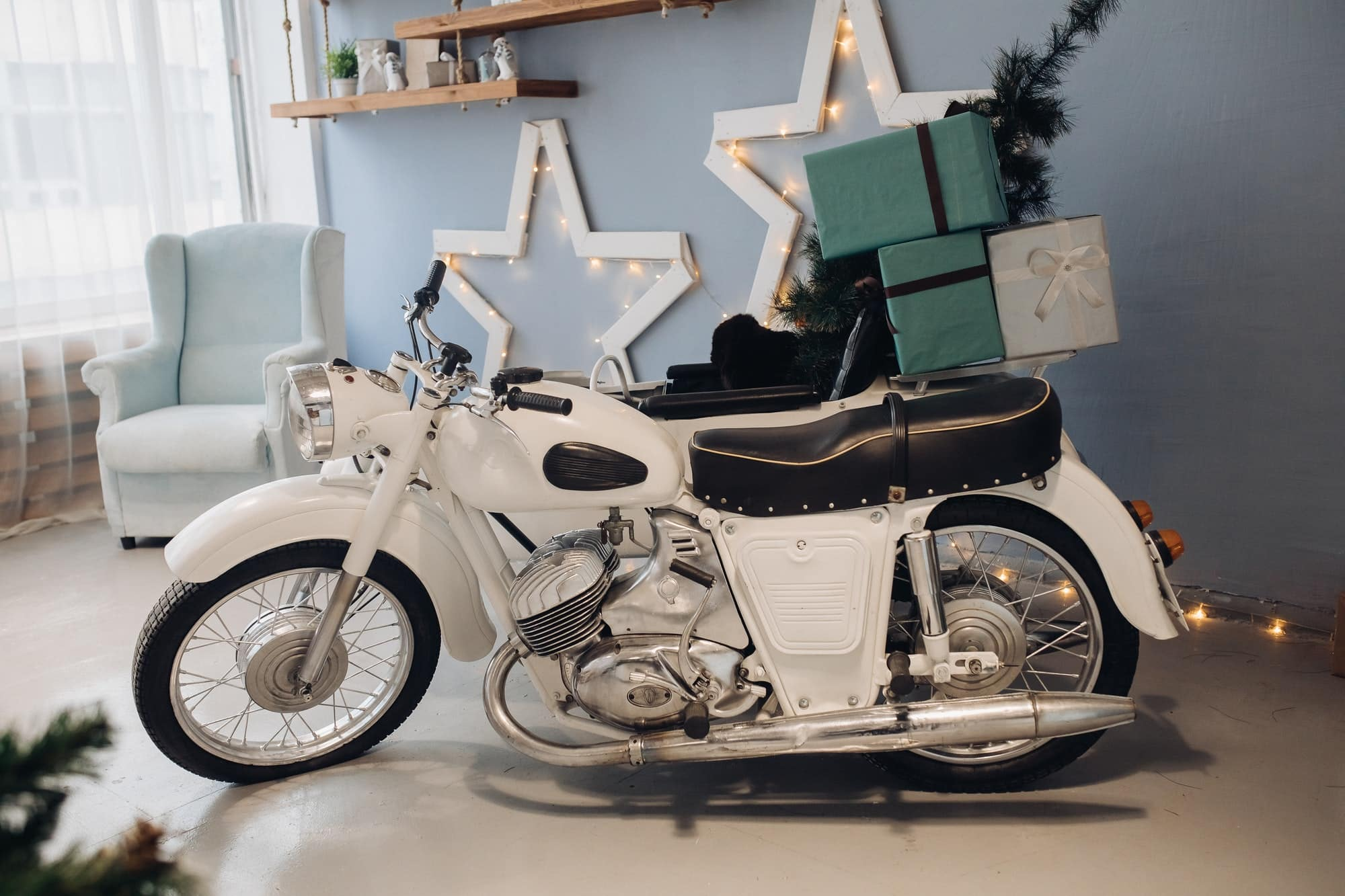 Cool retro motorcycle with Christmas presents. Motorcycle with gifts in decorated room