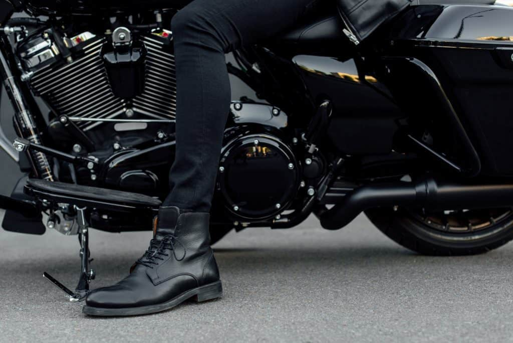 cropped view of man in black boot sitting on motorcycle