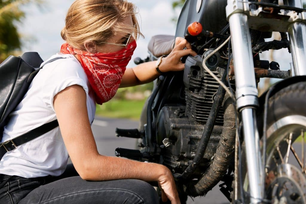 Professional young female biker in casual clothing, wears bandana covedred face, tries to solve mech