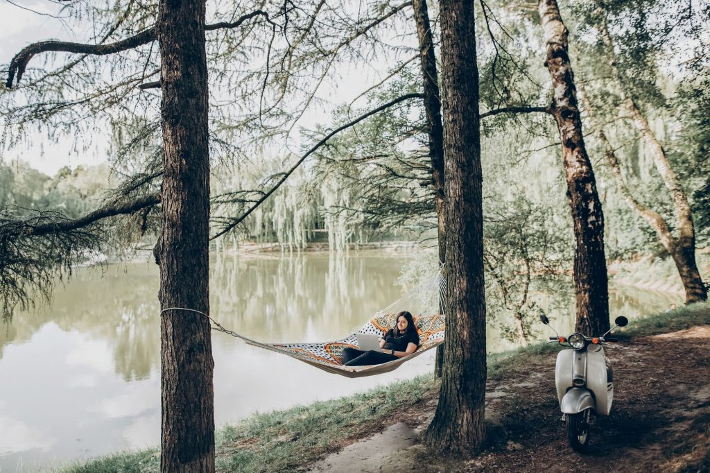 Freelancer working in the park while resting in hammock